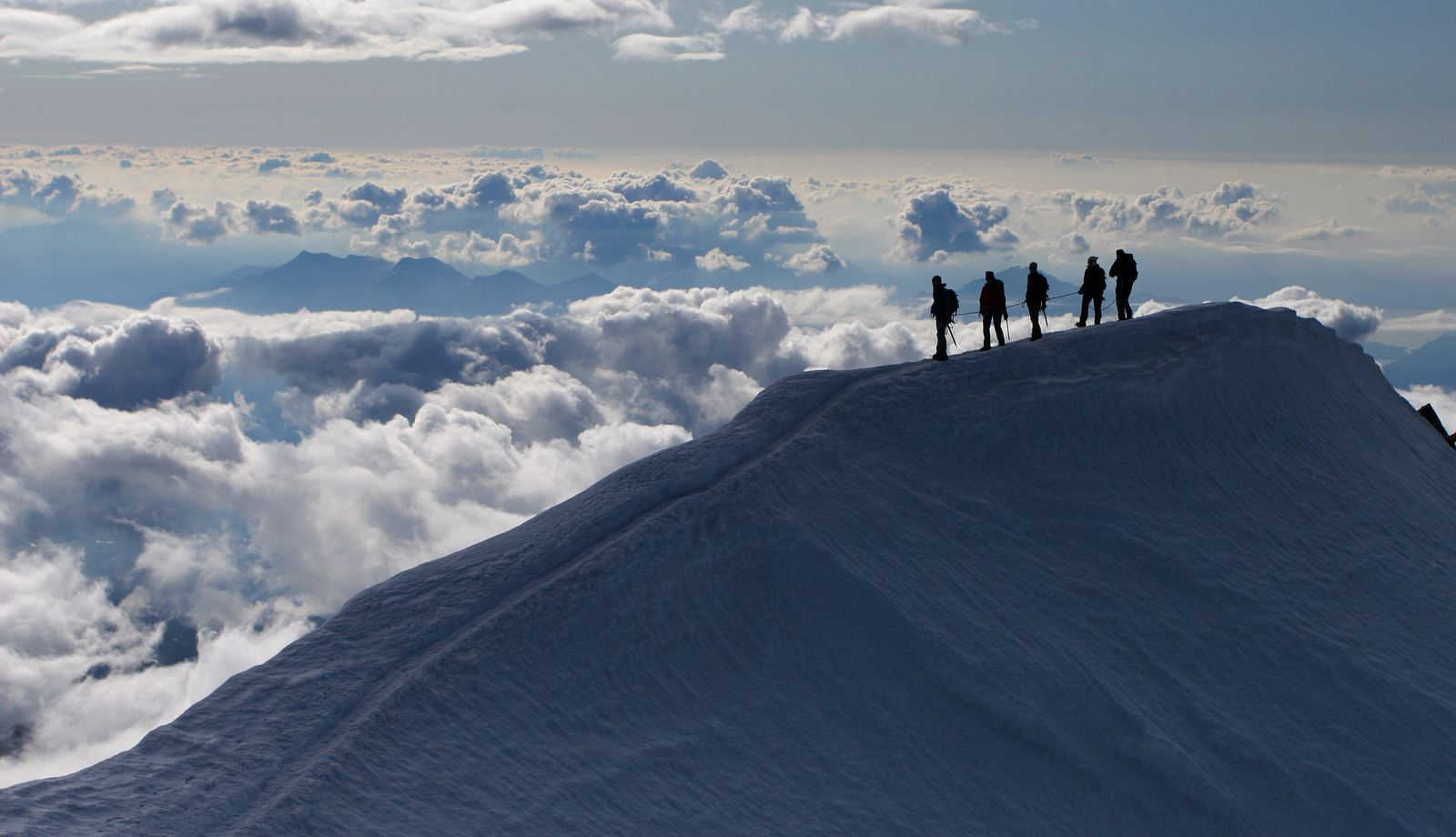 Five mountain climbers on an exposed snow ridge